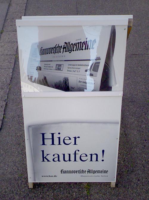 Werbetafel vor einem Kiosk in Hannover mit Werbung für die Hannoversche Allgemeine Zeitung. Der Text ist einfach nur die Aufforderung: Hier kaufen!