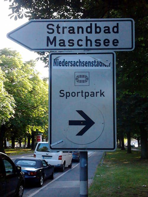 Korrigiertes Verkehrsschild. Der Text 'AWD-Arena' wurde mit dem Text 'Niedersachsenstadion' überklebt