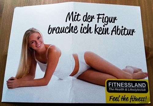 Werbeprospekt eines Fitness-Studios: Bild einer sich auf dem Boden räkelnden, schlanken Frau in Unterwäsche, die blau und blondäugig in die Kamera lächelt, dazu der Text 'Mit der Figur brauche ich kein Abitur'.