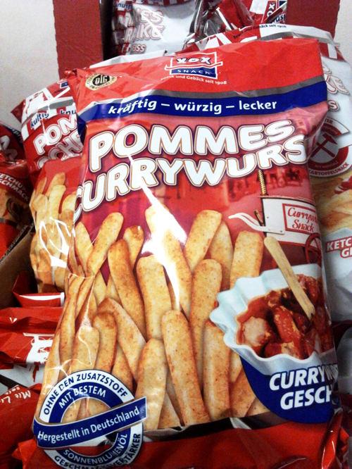 Verpackungstüte eines Junkfood-Produktes mit dem Namen 'Pommes Currywurst kräftig, würzig, lecker' mit Currywurst-Geschmack und der stempelartig aufgedruckten Zusicherung 'Ohne den Zusatzstoff Geschmacksverstärker. Mit bestem Sonnenblumenöl. Hergestellt in Deutschland'.