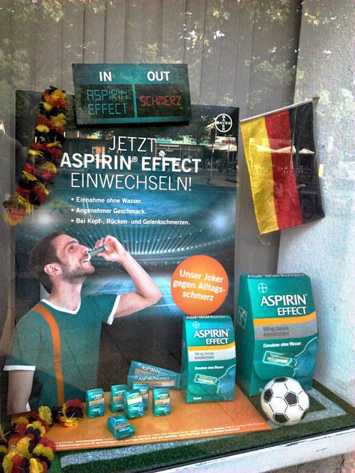 Obskure Aspirin-Reklame im Schaufenster einer Apotheke... mit Fußball. Der bedruckte Aufständer ist mit einer schwarz-rot-goldenen Flagge und einer schwarz-rot-goldenen Girlande verziert. Auf dem Aufständer ein Mensch in Fußballbekeidung, der sich vor einem leeren Großstadion 'Aspirin direkt' reinkippt. Dazu der Text: 'Jetzt Aspirin Direkt einwechseln -- Einnahme ohne Wasser -- Angenehmer Geschmack -- Bei Kopf-, Rücken- und Gelenkschmerzen -- Unser Joker gegen Alltagsschmerz'.
