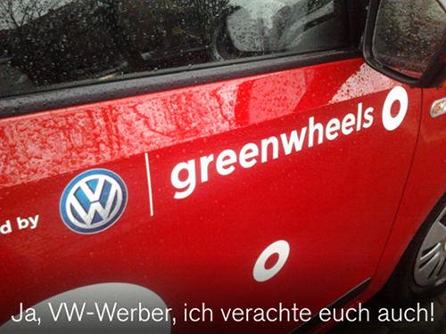 Auto mit Reklameaufdruck 'Powered by VW Greenwheels', darunter mein Text: 'Ja, VW-Werber, ich verachte euch auch!'.