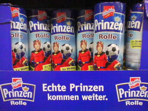 Verpackte Kekse der Marke 'Prinzen Rolle' mit einem Verpackungsmotiv eines gekrönten Prinzen, der einen Fußball in seiner rechten Hand hält. Auf dem Karton ist 'Echte Prinzen kommen weiter' gedruckt.