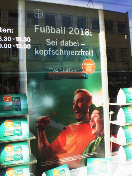 Werbung im Schaufenster einer Apotheke -- BAYER -- Fußball 2018: Sei dabei, kopfschmerzfrei! -- Aspirin Effect -- Einnahme ohne Wasser