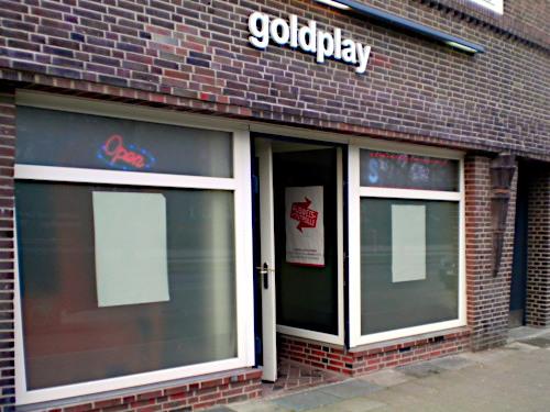 """Schäbige, heruntergekommene Spielhalle mit Fenstern, durch die man nichts sehen kann, über der Tür der Schriftzug """"Goldplay""""."""