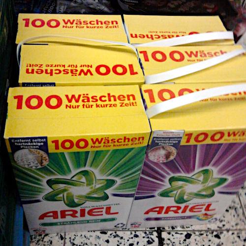 Waschmittelpackungen 'Ariel' in einem Supermarkt. Auf den Paketen ist aufgedruckt: '100 Wäschen -- Nur für kurze Zeit!'.