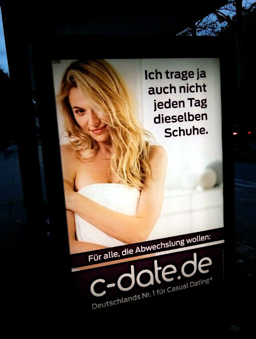 Beleuchtete Werbung am Straßenrand. Eine aufreizend blickende blonde Frau, die nur mit ihrem Handtuch bekleidet zu sein scheint. Dazu der Text: Ich trage ja auch nicht jeden Tag dieselben Schuhe. -- Für alle, die Abwechslung wollen: c-date.de -- Deutschlands Nr. 1 für Casual Dating