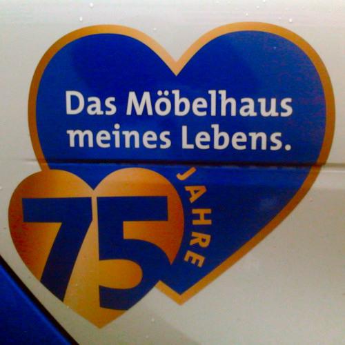 Werbung auf einem Firmenwagen eines großen hannöverschen Möbelhauses, angeordnet in zwei Herzen: 75 Jahre -- Das Möbelhaus meines Lebens.